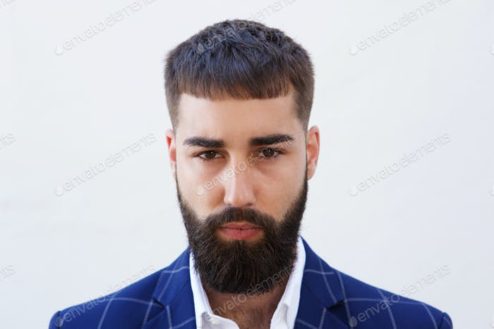 Close up serious businessman with beard staring