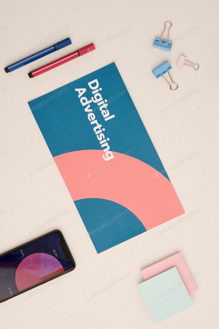 Flat layout of digital advertising brochure surrounded by office supplies