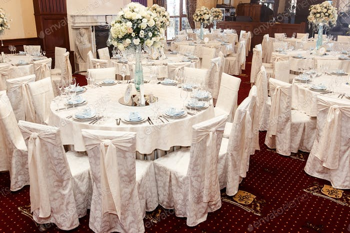 luxury wedding decor with flowers and glass vases with jewels on round tables