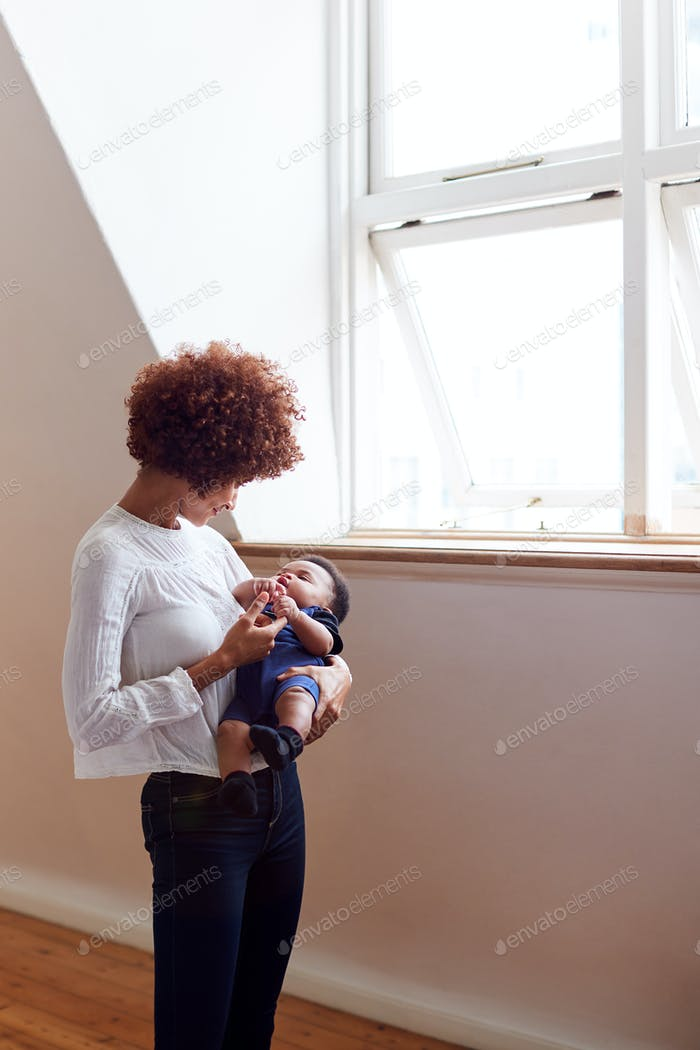 Loving Mother Holding Sleeping Newborn Baby By Window At Home In Loft Apartment
