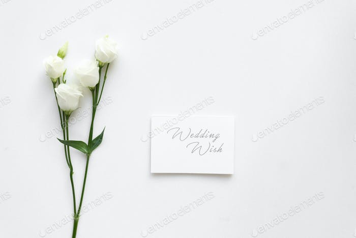 Wedding wish card with roses, on white marble. Top view.