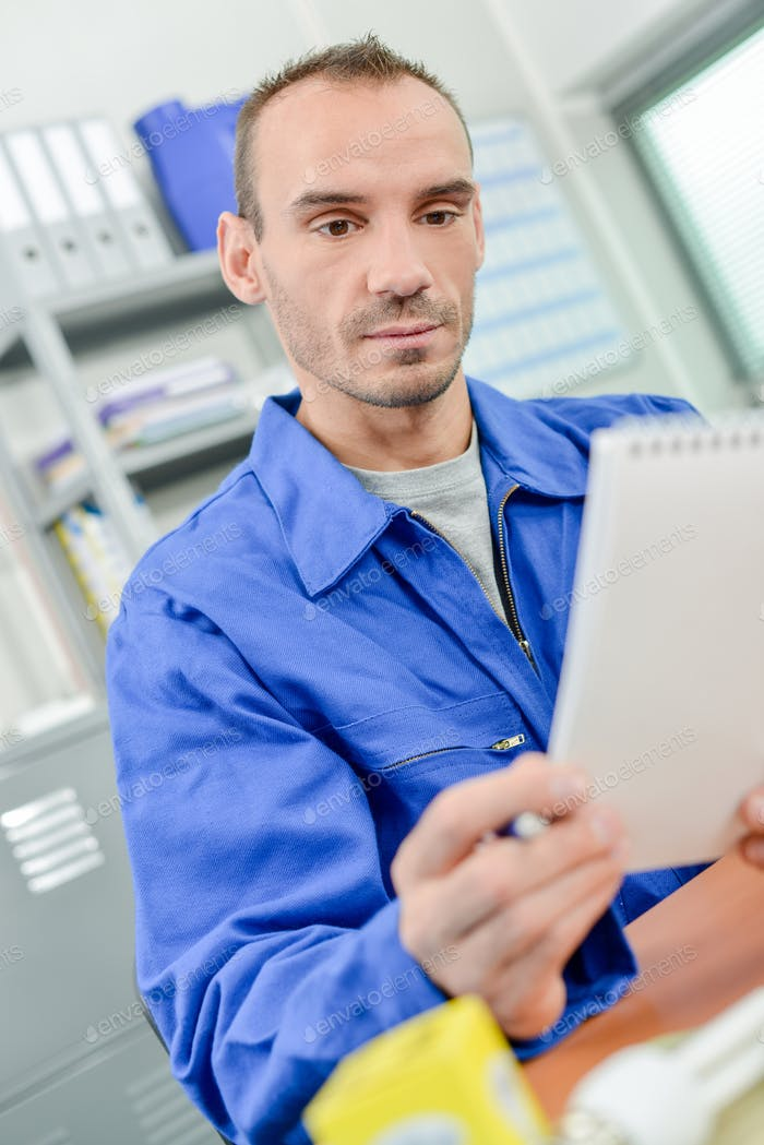 Man in overalls looking at notepad