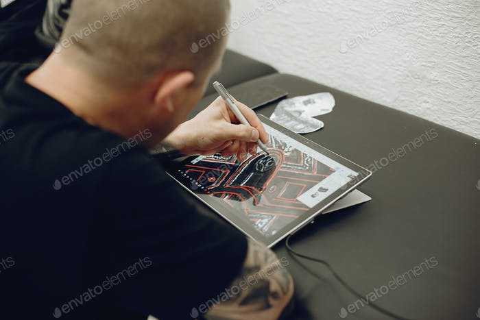 Man drawing the sketch in a tablet