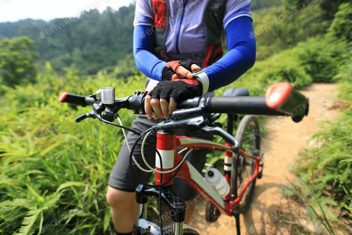 Cross country cyclist set smartwatch in the forest