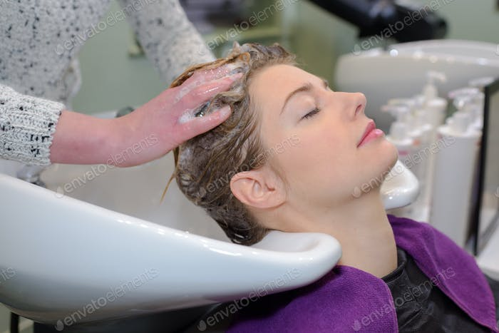 Woman having hair washed in salon