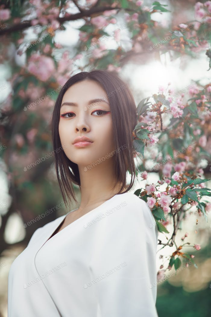 Asian woman outdoors on spring against flower blossom