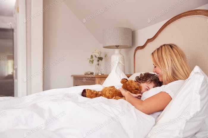 Mother And Young Son Wearing Pyjamas In Bedroom Together Playing With Cuddly Teddy Bear Toy
