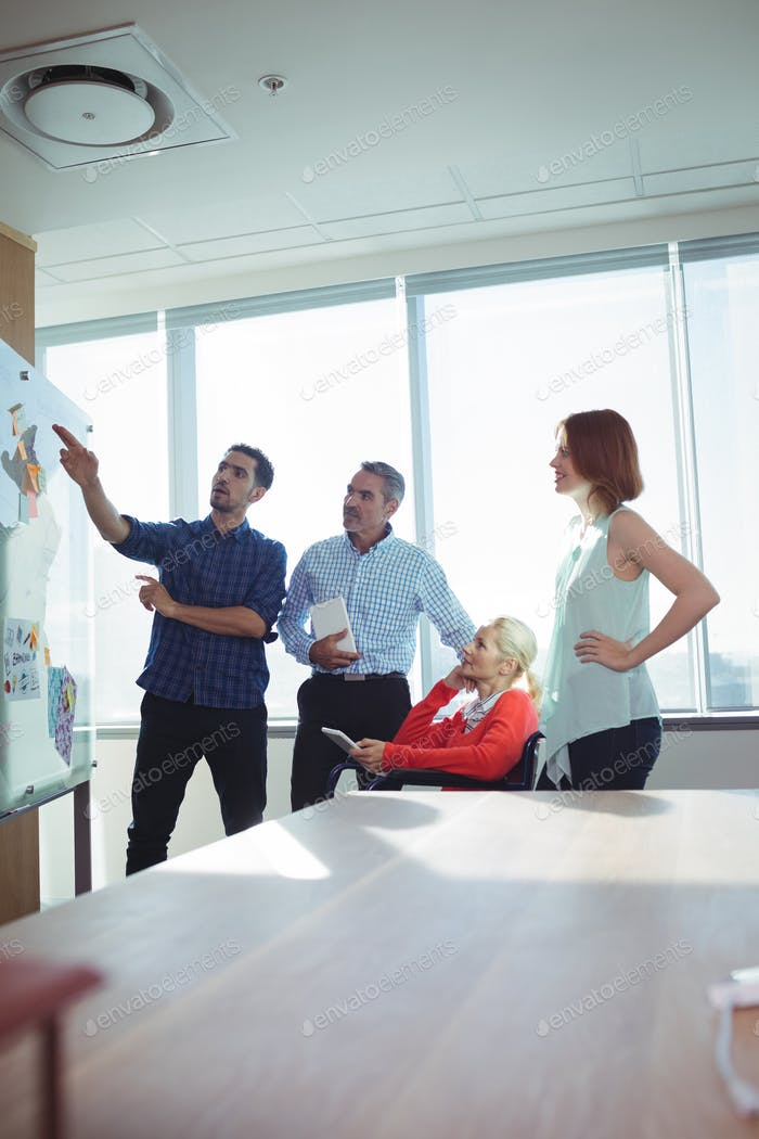 Businessman discussing with colleagues over whiteboard