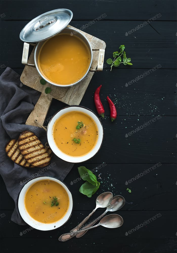 Red lentil soup with spices, herbs, bread in a rustic metal saucepan and bowls