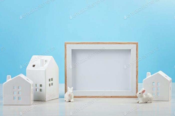 Pequeñas casas blancas con el marco de la maqueta con el espacio de copia para el texto. Casa nueva, Pascua, Navidad