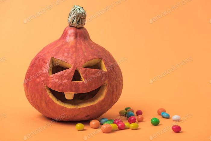 Geschnitzter Halloween-Kürbis mit Süßigkeiten auf orangefarbenem Hintergrund