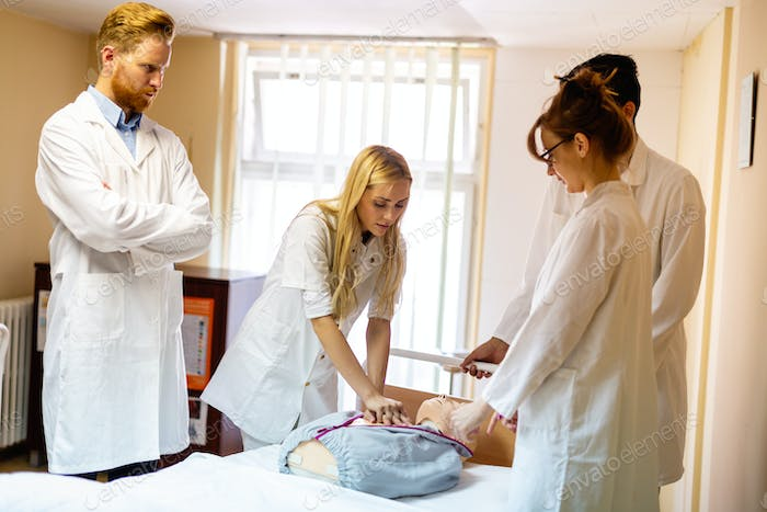 Group of medical students practicing reanimation task on model