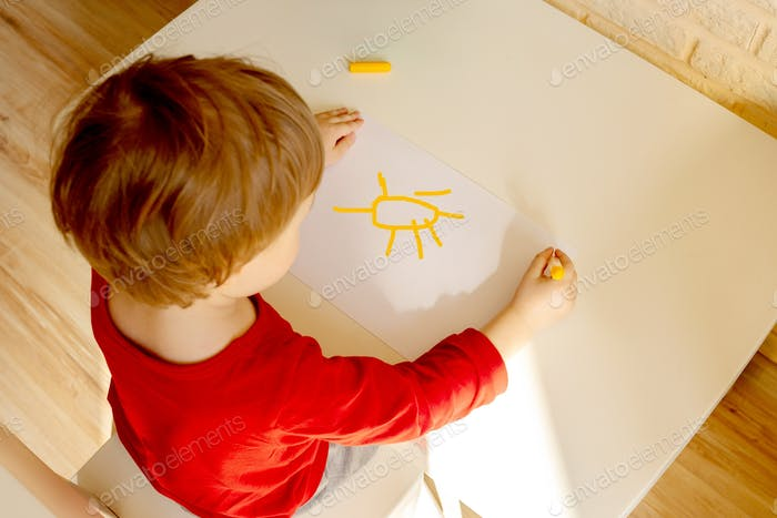 Junge zeichnet mit Filzstift im Album