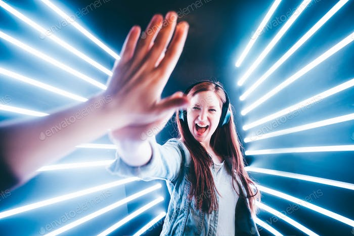 Friendly young people laughing and giving high five on neon background.