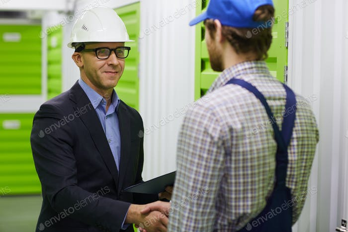 Business handshake in warehouse