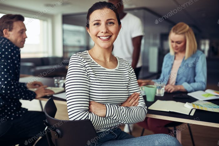 Smiling young businesswoman sitting with colleagues in an office