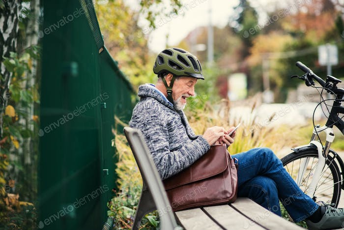 A senior man with electrobike sitting on a bench outdoors in town, using smartphone.