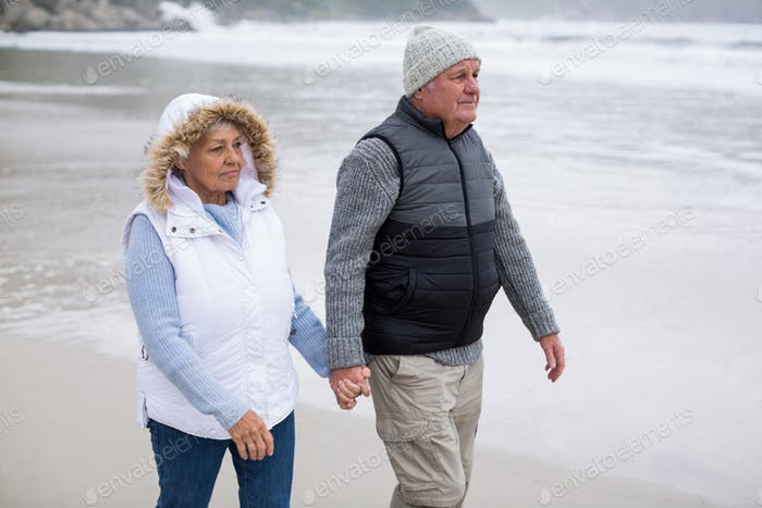 Senior couple walking toward the ocean while holding hands