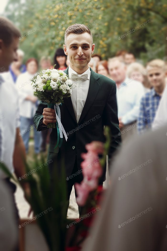 Handsome happy brunette groom in stylish black suit with white roses wedding bouquet