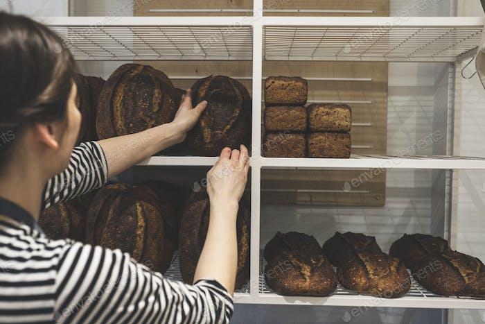 Artisan bakery making special sourdough bread, baker loading shelves with baked goods.