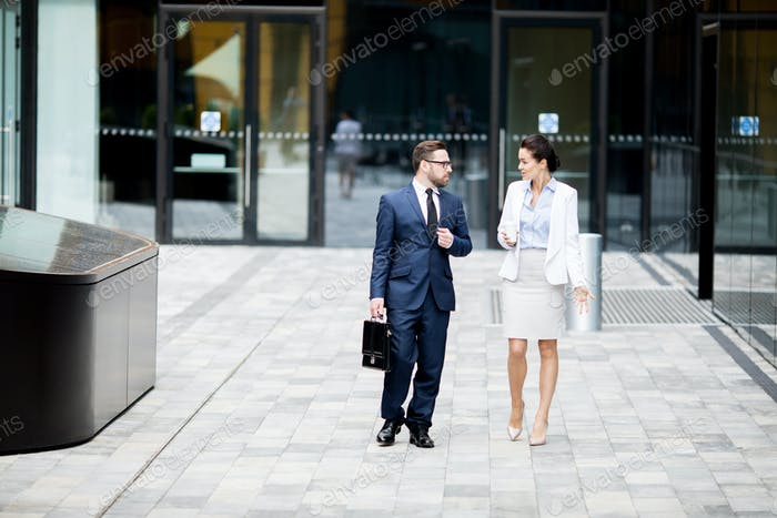 Formal man and woman getting out office building