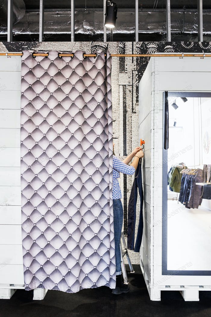 Woman hanging jeans in changing room at factory