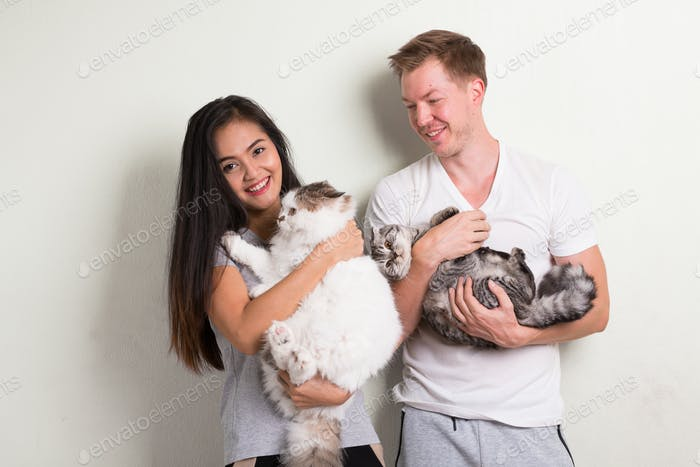 Young happy multi-ethnic couple holding two cats together against white background
