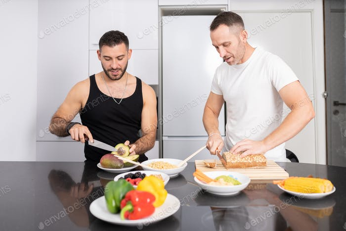 Gay couple cooking healthy vegan food together at home