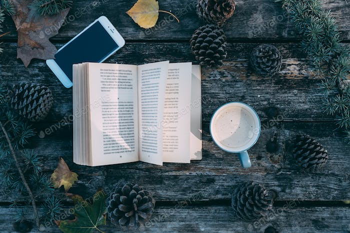 Book and mobile phone on a wooden table with coffee and pines ou