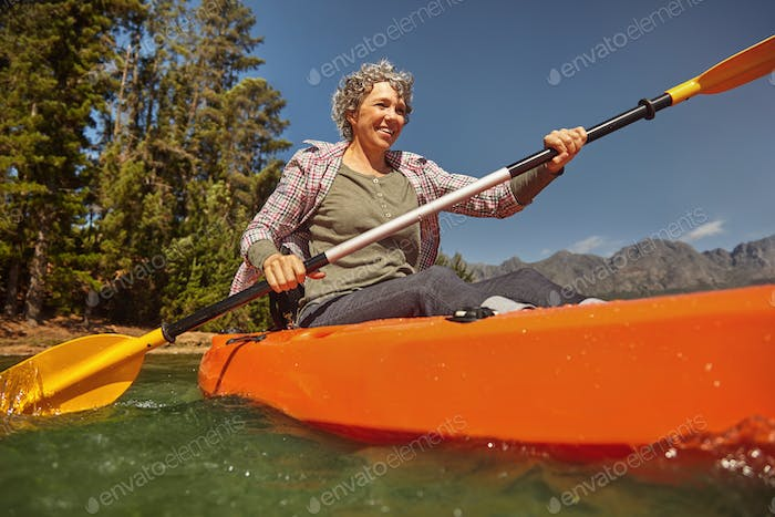Senior woman canoeing on summer day