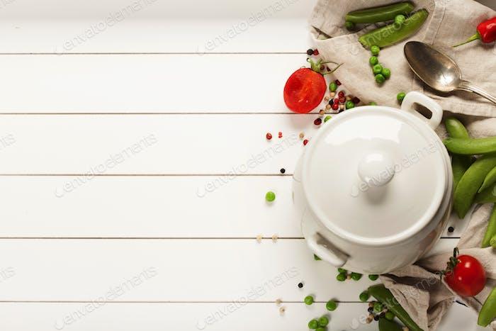 Weißer Kochtopf und Zutaten für Suppe oder Eintopf