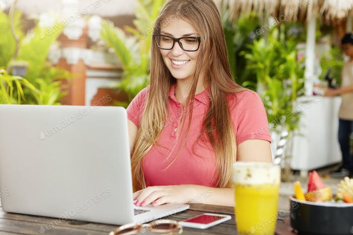 Junge Freiberuflerin in rechteckiger Brille mit Laptop für Remote-Arbeit, Keyboarding, Blick auf
