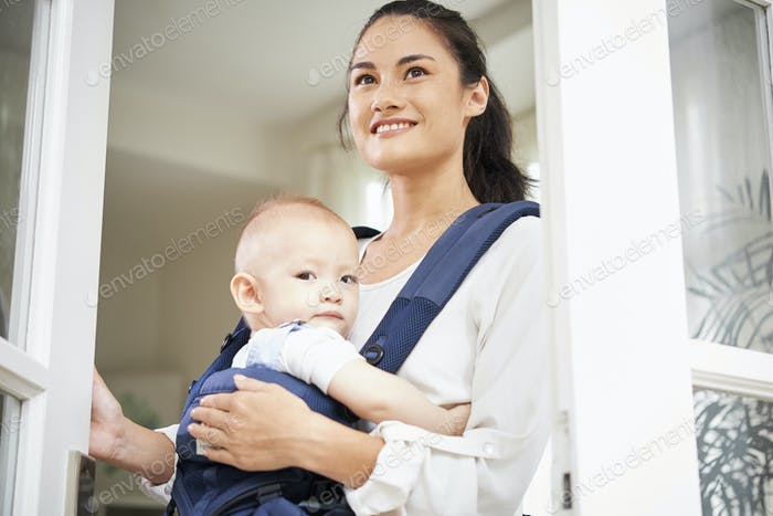 Cheerful woman with baby opening window