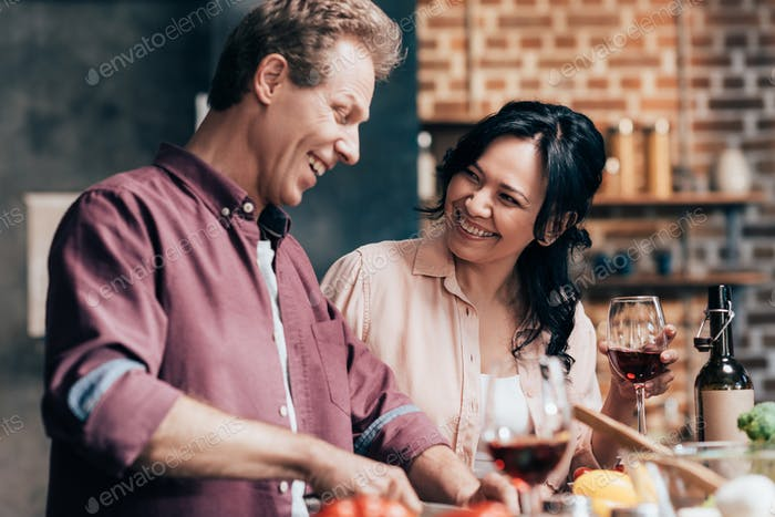 happy multiethnic couple preparing dinner together