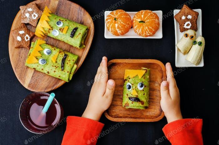 manos de los niños sosteniendo plato con el almuerzo en forma de monstruos