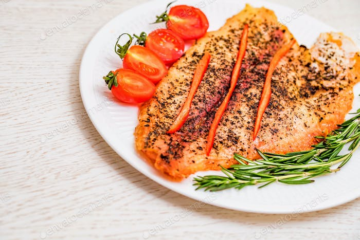 Roasted fish fillet with vegetables close