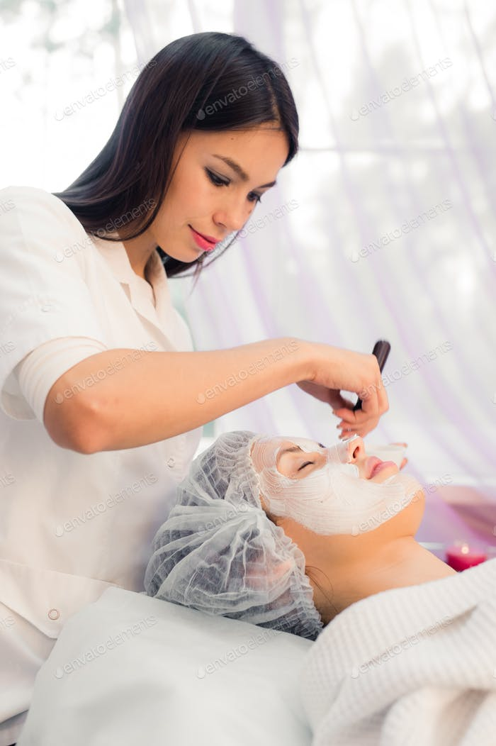 Young beautiful woman having spa procedure on her face