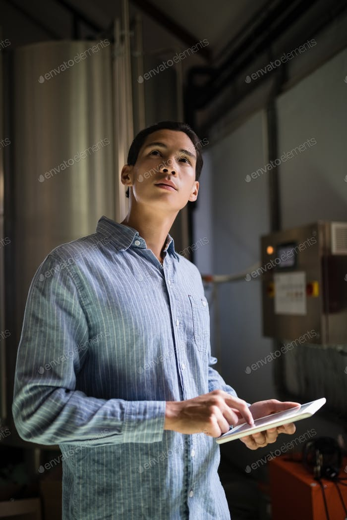 Manager using digital tablet in warehouse