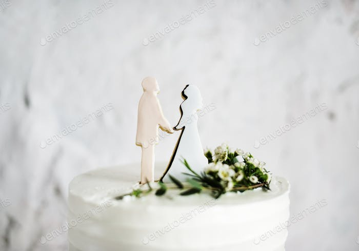 Closeup of  White Wedding Cake with Bride and Groom Figure Toppe