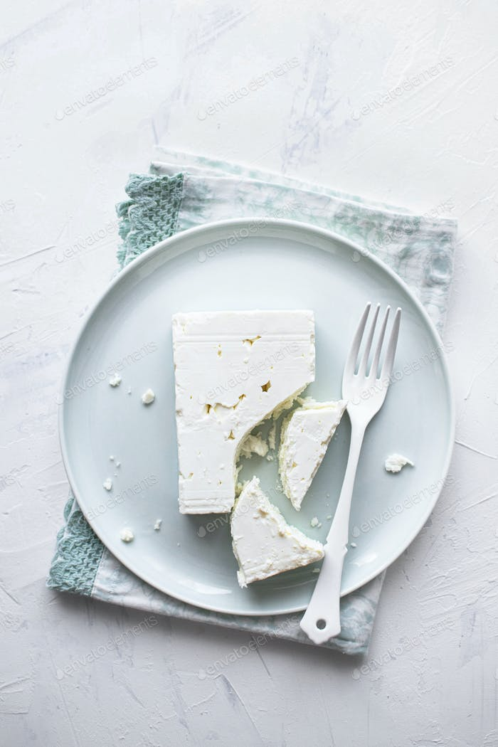 Feta cheese on a  white plate with fork flat lay