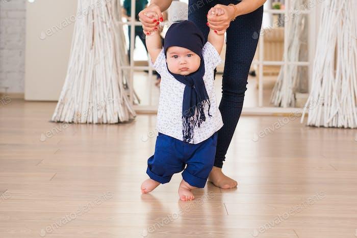 Mutter hält Babys Hände, um ihm zu helfen, zu gehen. Konzept des ersten Schrittes