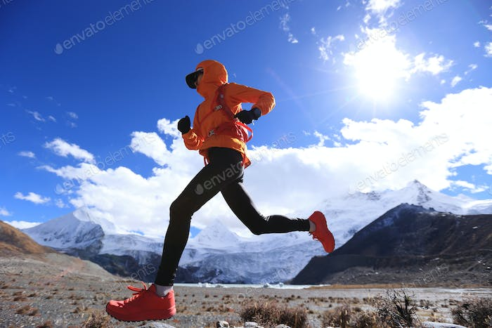 RunningWoman trail runner cross country running in high altitude winter nature