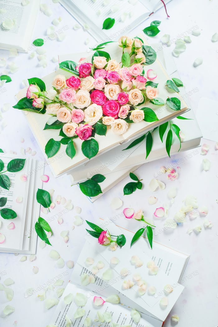Stack of white books with flowers and petals. Spring reading concept. Feminine still life in high