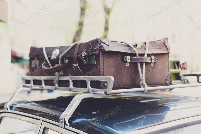 Vintage suitcase on an old car roof rack.