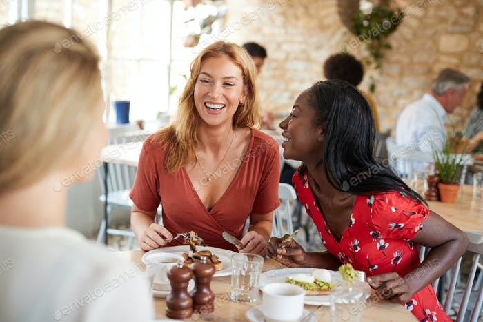 Three female friends talking over brunch at a cafe, close up