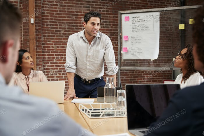 Mature Businessman Standing And Leading Office Meeting Around Table