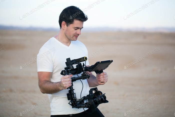 Young man using steadycam for shooting on beach