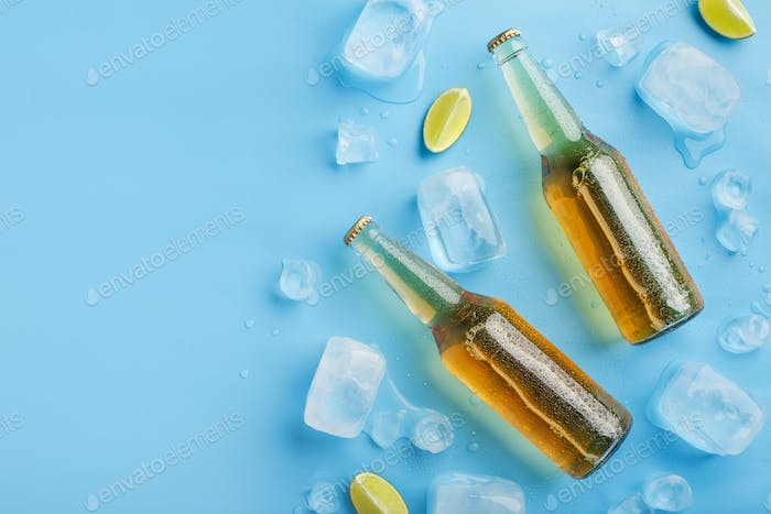 Two cold bottles of light beer without label with ice and pieces of lime on blue background