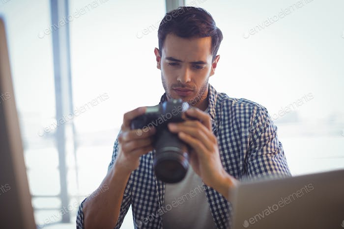 Photo editor holding camera while sitting in office