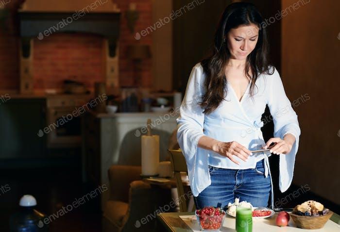 Mujer haciendo foto móvil de alimentos saludables para su blog de Internet